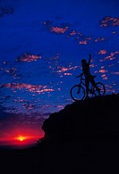 Silhouette of a young woman with a bicycle standing with her arm outstretched on top of a mountain peak with a purple sky and orange sun in the backgr...