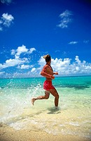 Man in shorts at the beach, jogging through shallow water