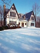 Exterior view of multi-story Tudor style house on a snowy day decorated with wreaths and red ribbons. Property released.