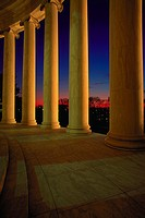 Marble columns in circular formation around building at night, with night lighting.