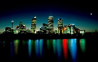 City skyline of Sydney, Australia in late evening with the colorful city lights reflecting off the calm harbor water.