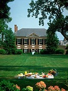 Portrait of the main hose at Woodlawn Plantation in Virginia with a large green lawn. In the foreground on the law a picnic blanket and lunch are set ...