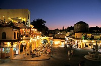 Old town at dusk in Plateia Ippokratous, Rhodes, Greece. Lit buildings surround town square.