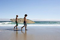 Teenage Boys Carrying Surfboards Down Beach