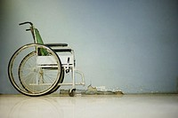 Empty Wheelchair by Cracked Wall