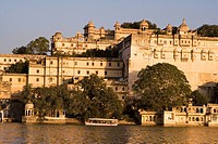 Tour boat on Lake Pichola in front of the City Palace. Udaipur. Rajasthan. India.