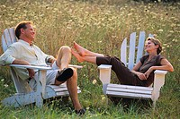 Couple Relaxing in Adirondack Chairs