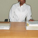 Businesswoman Looking Over Documents at Her Desk (thumbnail)