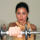 Focused Woman Lifting Dumbbell