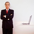 Businessman Standing next to Laptop and Cell Phone
