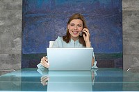 Businesswoman Using Cell Phone and Laptop