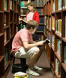 Students Reading in Library Aisle