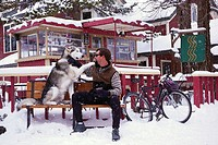 Man and Dog Sitting in Snowfall