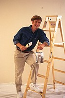 Painter Standing on Ladder with Paint Can and Brush