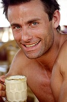 Portrait of goog-looking caucasian man drinking coffee and smiling at camera