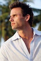 Profile shot of good-looking man with palm trees in background