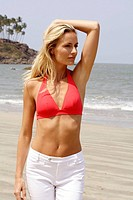 Portrait of beautiful blonde woman in red bikini top and white pants walking on a beach in India