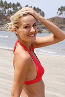 Portrait of good_looking blonde woman in red bikini top on beach in India