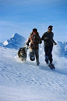 Couple Running with Dog Across Snow