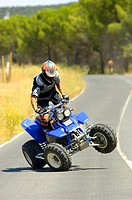 Man driving a quad on a lonely road
