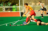 field hockey woman player running with the stick and the ball the other player is on the field
