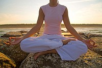 Young woman doing yoga exercises by sea (thumbnail)