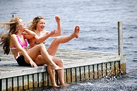 sisters 13 and 18 kicking up water while sitting on dock at lake