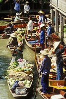 Thai floating market. In Damnoen Saduak, 100 Km from Bangkok, a place with canals where people live in palafittes, travel in boats and celebrate a mar...