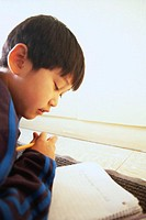 Boy Writing in a Notebook