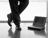 Legs of a Businessman Standing by Laptop Computer