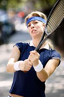 Caucasian woman tennis player swinging tennis racket