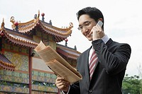 Businessman using mobile phone and reading newspaper