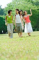 Four young women walking in park