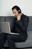Businessman sitting on sofa, using mobile phone and looking at laptop