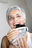 Senior, chocolate blackboard, bites off,  pleasure-fully, portrait  Series, women portrait, seniors, woman, well Age, well Ager, 60-70 years, happily,...