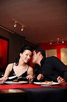 Man whispering into his girlfriend's ear while having dinner in a restaurant (thumbnail)