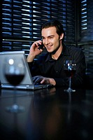 Man talking on the mobile phone while using laptop in the restaurant
