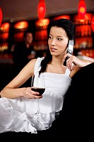 Woman talking on the mobile phone while holding a glass of wine