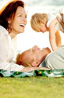 Couple and their lovely daughter having fun in the park