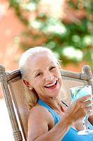 Woman smiling while holding a glass of drink