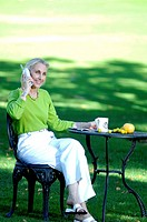 Woman talking on the phone while enjoying a cup of coffee in the garden