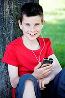 Boy leaning against a tree while listening to portable MP3 player