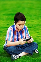 Boy with headphone and a handheld game device