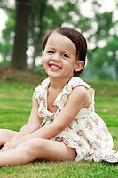 Little girl sitting on the grass,smiling