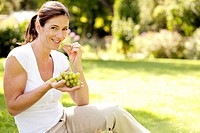 Woman enjoying green grapes in the park