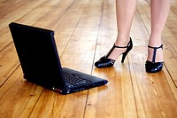 Woman in high heels with laptop on the floor