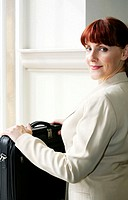 Businesswoman with laptop bag looking at the camera