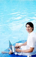 Man sitting on the pool side using laptop