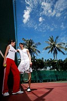 Couple talking in the tennis court