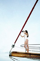 Woman using binoculars while sailing on yacht